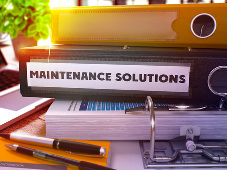 qualitatively: Black Office Folder with Inscription Maintenance Solutions on Office Desktop with Office Supplies and Modern Laptop. Maintenance Solutions Business Concept on Blurred Background. 3D Render.