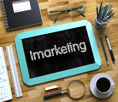 monetizing: Business Concept - Imarketing Handwritten on Mint Small Chalkboard. Top View Composition with Chalkboard and Office Supplies on Office Desk. Imarketing - Text on Small Chalkboard. 3d Rendering.