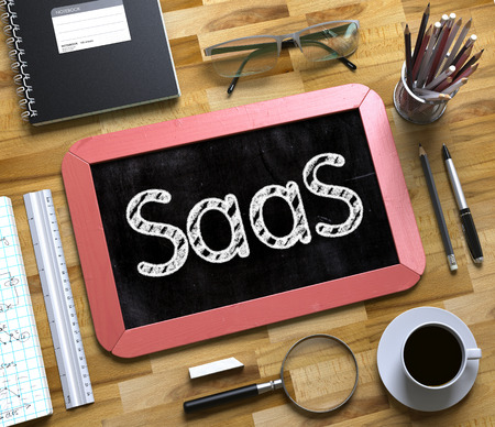 Saas Fee: Small Chalkboard with SaaS. SaaS - Red Small Chalkboard with Hand Drawn Text and Stationery on Office Desk. Top View. 3d Rendering.