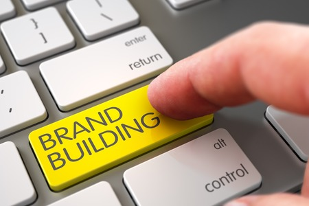 lifecycle: Business Concept - Male Finger Pointing Yellow Brand Building Key on Metallic Keyboard. 3D Illustration. Stock Photo