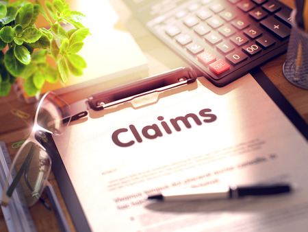 Claims on Clipboard with Sheet of Paper on Wooden Office Table with Business and Office Supplies Around. 3d Rendering. Blurred Image. Stock Photo