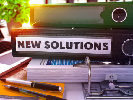 new solutions: New Solutions - Black Ring Binder on Office Desktop with Office Supplies and Modern Laptop. New Solutions Business Concept on Blurred Background. New Solutions - Toned Illustration. 3D Render. Stock Photo