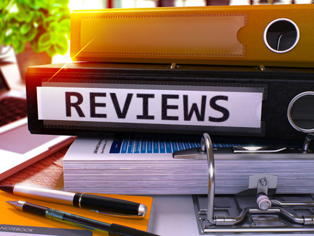 characterization: Reviews - Black Office Folder on Background of Working Table with Stationery and Laptop. Reviews Business Concept on Blurred Background. Reviews Toned Image. 3D.