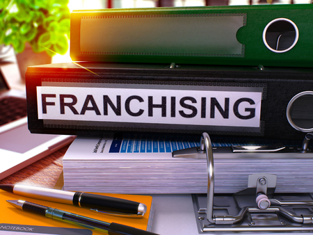 franchising: Black Office Folder with Inscription Franchising on Office Desktop with Office Supplies and Modern Laptop. Franchising Business Concept on Blurred Background. Franchising - Toned Image. 3D.