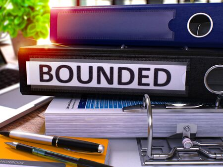bounded: Black Office Folder with Inscription Bounded on Office Desktop with Office Supplies and Modern Laptop. Bounded Business Concept on Blurred Background. Bounded - Toned Image. 3D. Stock Photo