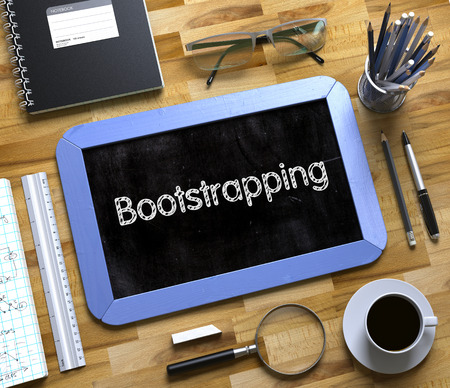 Bootstrapping - Text on Small Chalkboard.Top View of Office Desk with Stationery and Blue Small Chalkboard with Business Concept - Bootstrapping. 3d Rendering.