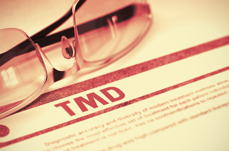 dolor de oido: TMD - Temporomandibular Disorder - Printed Diagnosis with Blurred Text on Red Background with Pair of Spectacles. Medical Concept. 3D Rendering.
