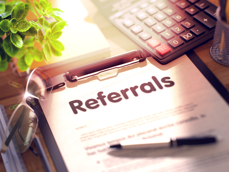 referrals: Referrals on Clipboard. Office Desk with a Lot of Office Supplies. 3d Rendering. Blurred and Toned Illustration. Stock Photo