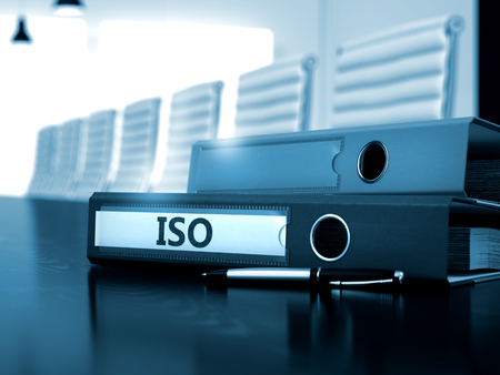 standardization: ISO - Business Concept on Blurred Background. ISO - File Folder on Office Wooden Desktop. ISO - Concept. 3D. Stock Photo