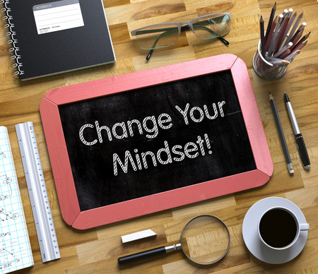 Change Your Mindset - Red Small Chalkboard with Hand Drawn Text and Stationery on Office Desk. Top View. Change Your Mindset - Text on Small Chalkboard. 3d Rendering. Stock Photo