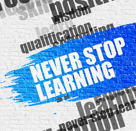 Never Stop Learning on White Brickwall. Motivational Concept. Stock Photo