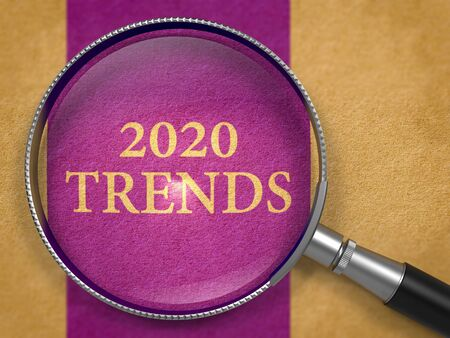 2020 Trends Concept through Magnifier or Magnifying Glass on Purpule Paper with Dark Lilac Vertical Line Background. Business Concept.