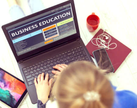 Business Education. Young Woman Writes a Text on Modern Portable Ultrabook Keyboard with Open Educational Web Page While Having Recreation Time at Home. Self-education Concept. Imagens