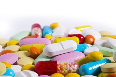 investigated: Colorful diferent tablets mix heap drugs, pills, capsules on white background