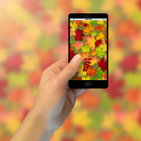 realistic hand holding a phone, takes pictures of autumn leaves, blurred background