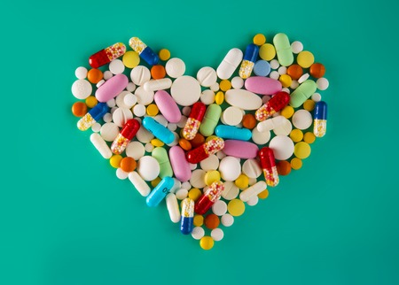 antibiotic pink pill: Multicolored pills and tablets, heart shape on green background