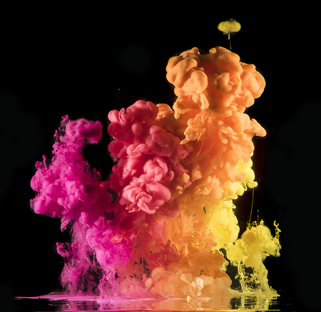 Colorful rainbow paint drops from above mixing in water. Ink swirling underwater. 免版税图像