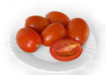 comestible: Tomatoes in the drops of dew on a white plate. Stock Photo