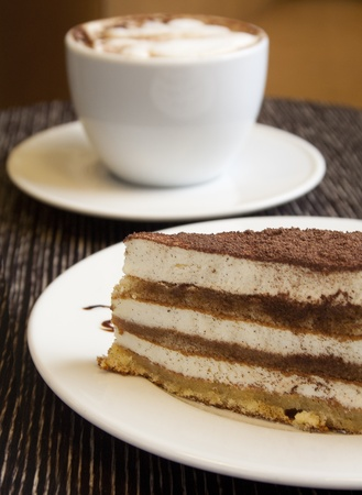 custard slices: A piece of chocolate cake in the foreground  Behind a cup of cappuccino is not in focus