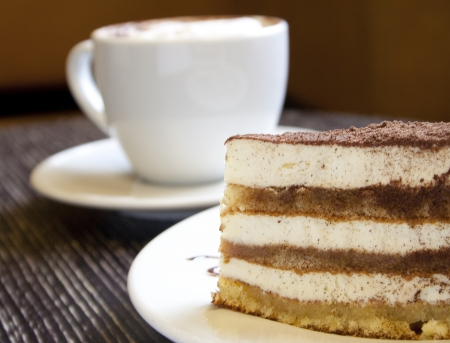 A piece of chocolate cake in the foreground  Behind a cup of cappuccino is not in focus