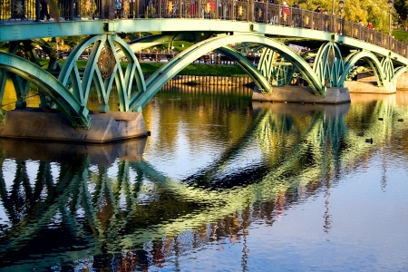 Part of the metal bridge with arches and its reflection in the water  Stock Photo