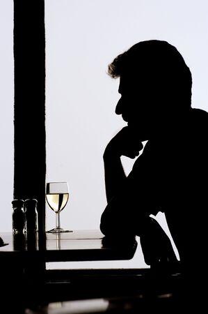 hombre solitario: Hombre solo que se sienta con el vino Foto de archivo