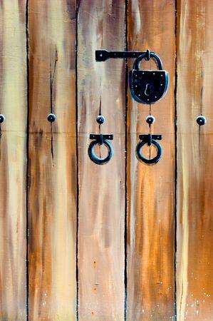Antique padlock on wooden door photo
