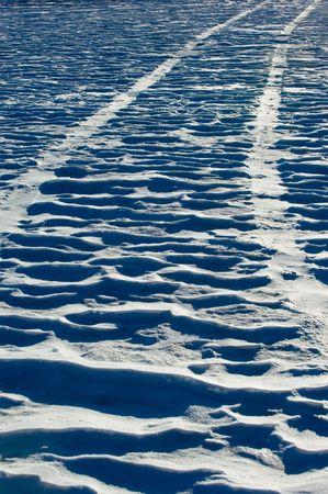Tire traks on snow field photo