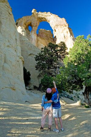 national scenic trail: Young tourists looking at Grosvenor Arch, Escalante national monument, Utah
