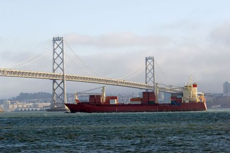 Crgo ship under Bay bridge with San Francisco on background photo