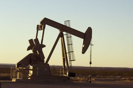 Working oil pump in rural Texas at sunset photo