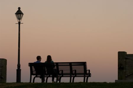 Couple sitting on the bench watching sunset by Mississippi river in New Orleans photo