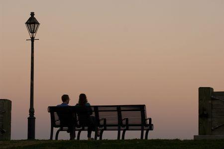 Echtpaar zittend op de bank kijken zonsondergang door de Mississippi rivier in New Orleans