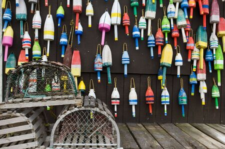 Lobster traps and colorful buoys on fishermans house in coastal Maine