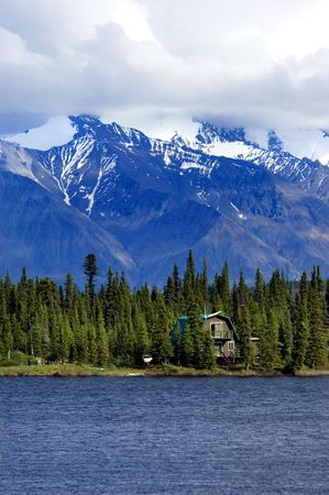 the mountain range: House on Alaskan lake with mountain range on background Stock Photo