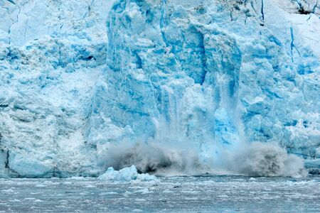 climate change: Ice falling from glacier in Alaska illustrating climate change