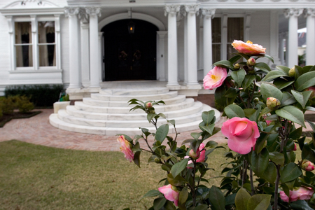 White mansion with flowers on foreground in New Orleans Garden district