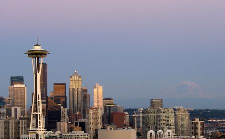 highrises: Seattle highrises with Space needle and mount Rainier in the evening Stock Photo