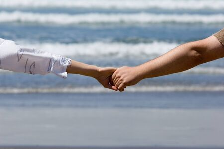 Young couple hands with the ocean waves background