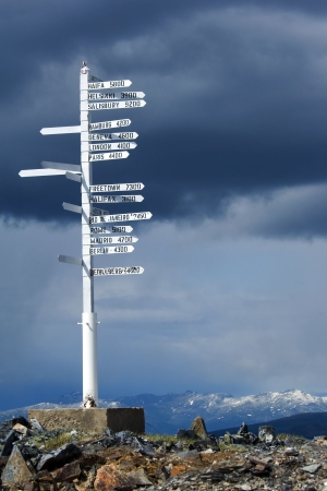 in distance: Direction pole with world cities signs on the top of Alaskas mountain Stock Photo
