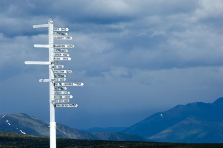 distance: Direction pole with world cities signs on the top of Alaskas mountain Stock Photo