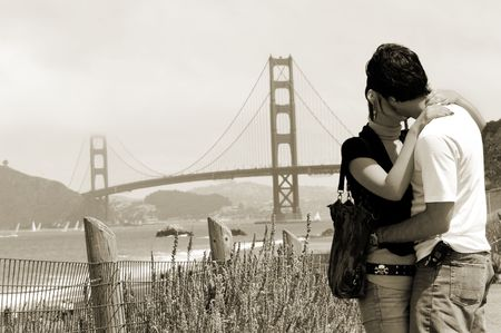 Young couple with Golden Gate bridge on background, San Francisco