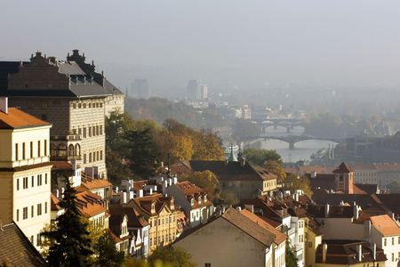 Red roofs of old Prague houses in fall colors with view of Vltava river photo