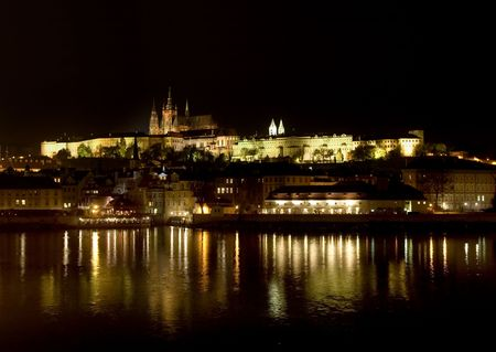 Hradcany and illuminated castle at night reflecting in Vltava, Prague photo