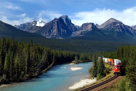 forest railroad: Freight train moving along Bow river in Canadian Rockies Stock Photo