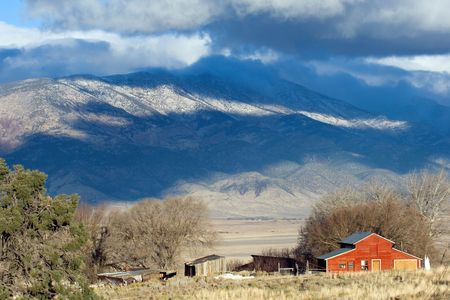 ranch house: Red ranch house in Nevada state with mountain range on background