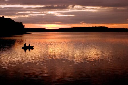 Father and son fishing on rural lake at sunset photo