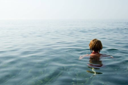 Girl swimming in crystal clear water of Black Sea, Ukraine photo