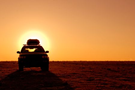 dirty car: Offroad 4x4 vehicle in the desert at sunrise