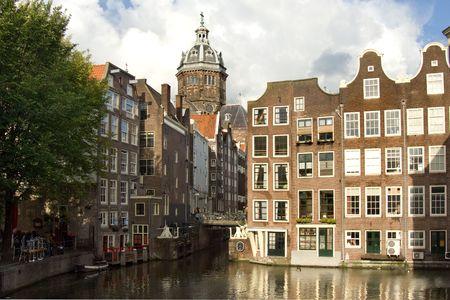 house gables: Iglesia y casas comerciales a lo largo del canal de Amsterdam